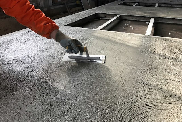 operaio cosmoseri al lavoro durante lisciatura del cemento